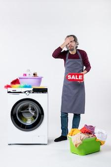 Vorderansicht junger mann in schürze, der das verkaufsschild hochhält und die hand auf sein gesicht in der nähe des wäschekorbs der waschmaschine an der weißen wand legt