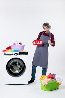 Vorderansicht junger mann in schürze, der ein verkaufsschild hochhält, das daumen hoch schild in der nähe des wäschekorbs der waschmaschine an der weißen wand macht