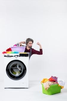 Vorderansicht junger mann in schürze, der hinter waschmaschine sitzt und stärke auf weißer wand zeigt