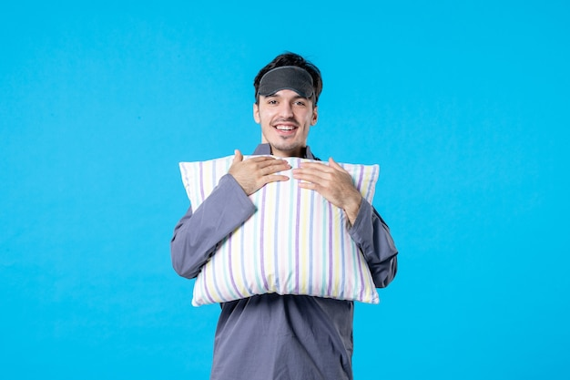 Vorderansicht junger mann in seinem pyjama, der kissen auf blauem hintergrund hält farbe albtraum mensch bett traum nachtruhe aufwachen spätschlaf lächeln