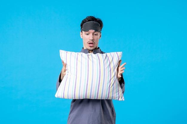 Vorderansicht junger mann in seinem pyjama, der kissen auf blauem hintergrund hält farbe albtraum mensch bett traum nachtruhe aufwachen spätschlaf