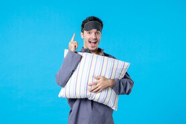 Vorderansicht junger mann in seinem pyjama, der kissen auf blauem hintergrund hält farbe albtraum menschliches bett idee nachtruhe aufwachen spätschlaftraum