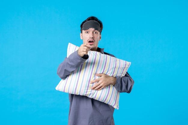 Vorderansicht junger mann in seinem pyjama, der kissen auf blauem hintergrund hält farbe albtraum menschliches bett nacht aufwachen spätschlaftraum