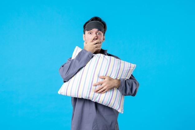 Vorderansicht junger mann in seinem pyjama, der kissen auf blauem hintergrund hält farbe albtraum menschliches bett nachtruhe aufwachen spätschlaf traum emotion überrascht