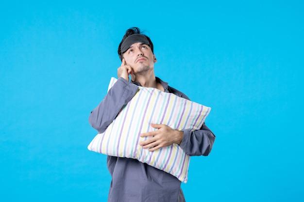 Vorderansicht junger mann in seinem pyjama, der kissen auf blauem hintergrund hält farbe albtraum menschliches bett nachtruhe wecken späte schlafträume