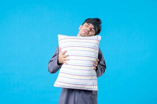 Vorderansicht junger mann in seinem pyjama, der kissen auf blauem hintergrund hält farbe menschliches bett traumschlaf nachtruhe alptraum spät aufwachen