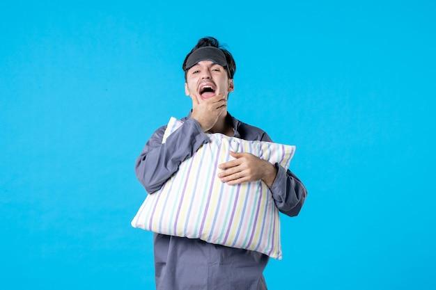 Vorderansicht junger mann in seinem pyjama, der kissen auf blauem hintergrund hält farbe späte müdigkeit albtraum menschliches bett nachtruhe wecken schlaftraum