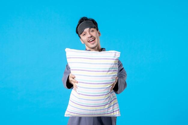 Vorderansicht junger mann in seinem pyjama, der kissen auf blauem hintergrund hält farben menschliches bett traum schlafen nachtruhe alptraum spät aufwachen