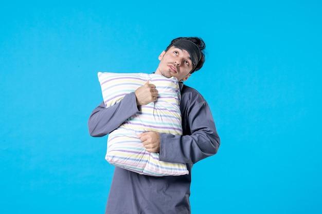 Vorderansicht junger mann in seinem pyjama, der kissen auf blauem hintergrund hält mensch bett traum schlaf nacht farbe ruhe alptraum aufwachen
