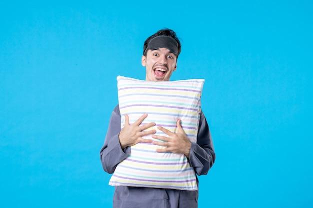 Vorderansicht junger mann in seinem pyjama, der kissen auf blauem hintergrund hält mensch traum schlaf nacht farbe bett albtraum spät aufwachen