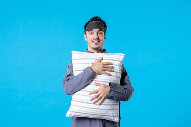 Vorderansicht junger mann in seinem pyjama, der kissen auf blauem hintergrund hält menschlicher traum schlafen nachtfarbe bettruhe albtraum spät aufwachen