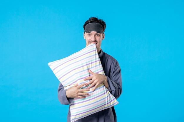 Vorderansicht junger mann in seinem pyjama, der kissen auf blauem hintergrund hält menschlicher traum schlafen nachtfarbe bettruhe spät aufwachen