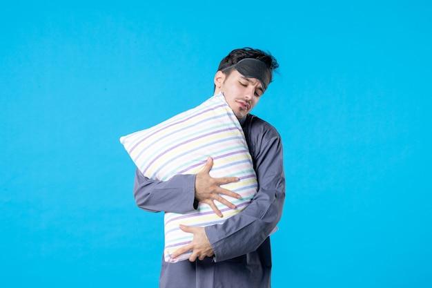Vorderansicht junger mann in seinem pyjama, der kissen auf blauem hintergrund hält menschliches bett traum schlafen nacht farbe ruhe alptraum spät aufwachen