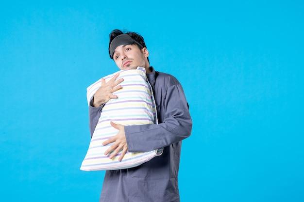 Vorderansicht junger mann in seinem pyjama, der kissen auf blauem hintergrund hält menschliches bett traum schlafen nacht farbe ruhe alptraum spät