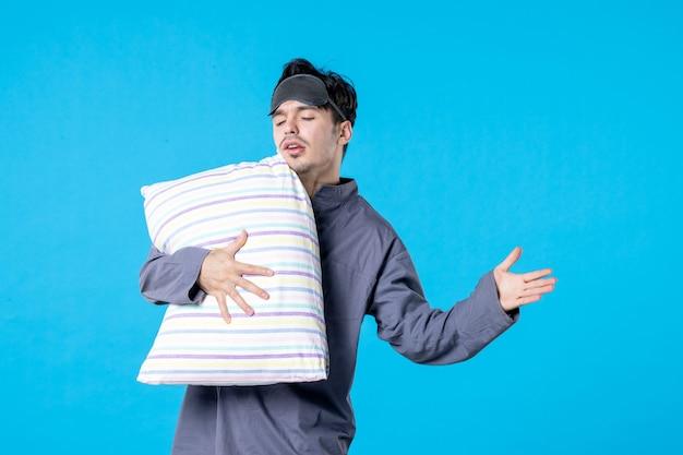 Vorderansicht junger mann in seinem pyjama, der kissen auf blauem hintergrund hält menschliches bett traumschlaf nachtruhe alptraum spät aufwachen