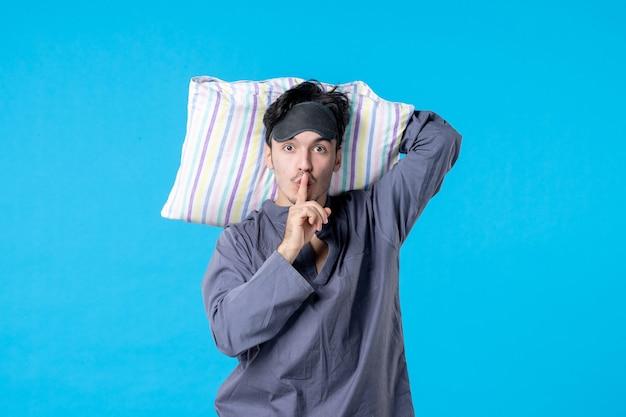 Vorderansicht junger mann in seinem pyjama, der kissen auf blauem hintergrund hält traumschlaf nacht spät bettruhe alptraum farbe aufwachen mensch