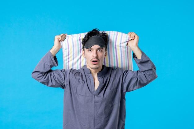 Vorderansicht junger mann in seinem pyjama, der kissen auf blauem hintergrund hält traumschlaf nacht spät bettruhe alptraum farbe aufwachen