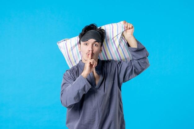 Vorderansicht junger mann in seinem pyjama, der kissen auf blauem hintergrund hält traumschlaf nacht spät mensch bettruhe alptraum farbe aufwachen ruhig