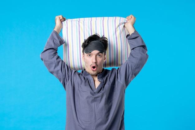 Vorderansicht junger mann in seinem pyjama, der kissen auf blauem hintergrund hält traumschlaf nacht spät mensch bettruhe alptraum farbe wachen