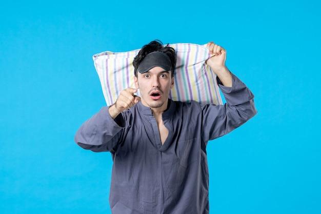 Vorderansicht junger mann in seinem pyjama, der kissen auf blauem hintergrund hält traumschlaf nacht spät menschliche ruhe alptraum farbe aufwachen