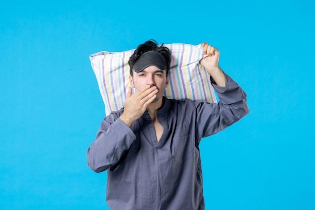 Vorderansicht junger mann in seinem pyjama, der kissen auf blauem hintergrund hält traumschlaf nacht spät menschliches bett alptraum farbe aufwachen