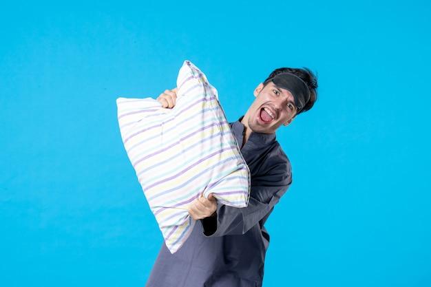 Vorderansicht junger mann in seinem pyjama, der kissen auf blauem hintergrund hält
