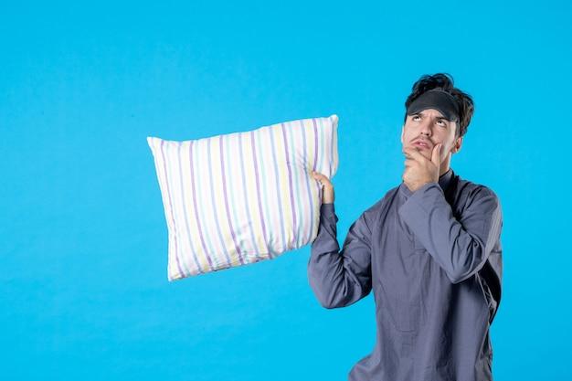 Vorderansicht junger mann in seinem pyjama, der kissen hält und auf blauem hintergrund denkt