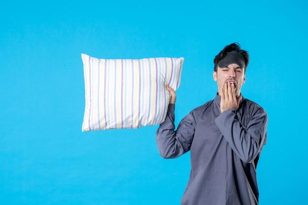 Vorderansicht junger mann in seinem pyjama, der kissen hält und auf blauem hintergrund gähnt