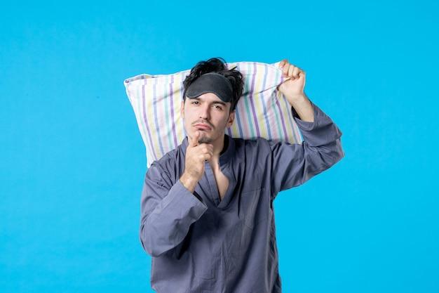 Vorderansicht junger mann in seinem pyjama, der kissen hält und mit seinem finger auf blauem hintergrund warnt