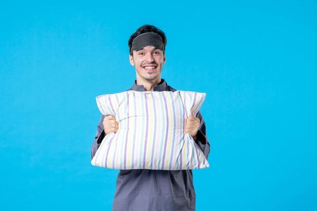 Vorderansicht junger mann in seinem pyjama mit kissen auf blauem hintergrund farbe albtraum mensch bett traum schlaf nachtruhe aufwachen spät