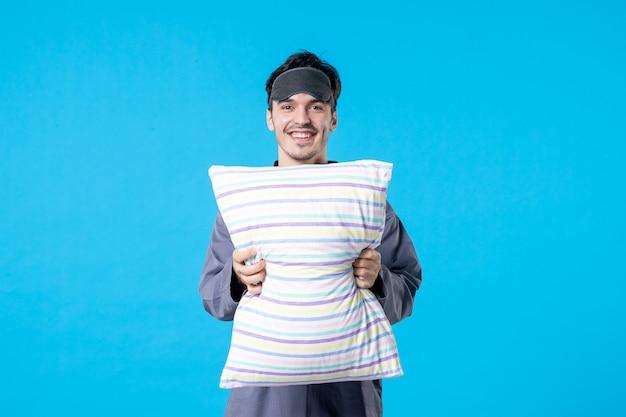 Vorderansicht junger mann in seinem pyjama mit kissen auf blauem hintergrund farbe bett traum schlaf nachtruhe alptraum spät aufwachen