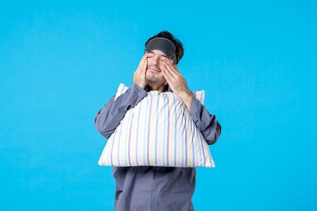 Vorderansicht junger mann in seinem pyjama mit kissen auf blauem hintergrund farbe spät alptraum menschliches bett nachtruhe wachen schlaf traum müde