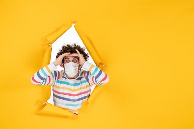 Vorderansicht junger mann in steriler maske auf gelbem covid-gesundheitsfoto des menschlichen pandemievirus