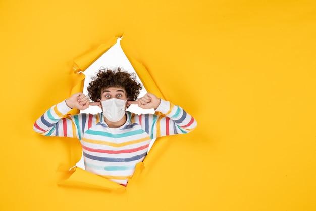 Vorderansicht junger mann in steriler maske auf gelber gesundheitsfarbe kovide menschliche fotopandemie