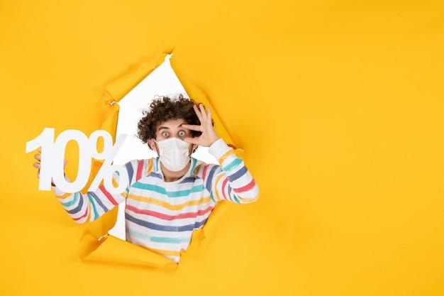 Vorderansicht junger mann in steriler maske mit schrift auf gelber gesundheitskovid-pandemie-verkaufsfarbe