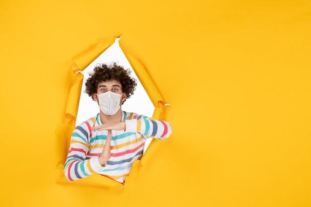 Vorderansicht junger mann in steriler maske mit t-zeichen auf gelbem gesundheitsfarbfoto covid-pandemischer virus mensch