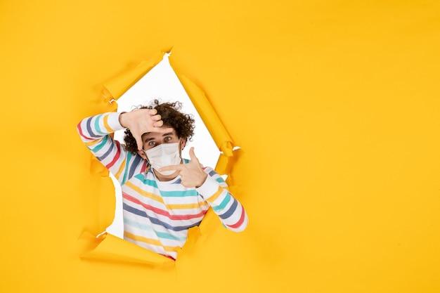Vorderansicht junger mann in weißer steriler maske auf gelb zerrissenem farbkovid-gesundheitsfotopandemievirus