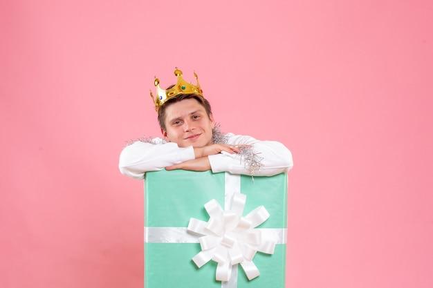 Vorderansicht junger mann innen vorhanden mit krone auf dem rosa hintergrund