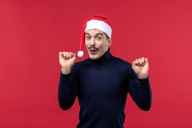 Vorderansicht junger mann mit aufgeregtem ausdruck auf rotem hintergrund