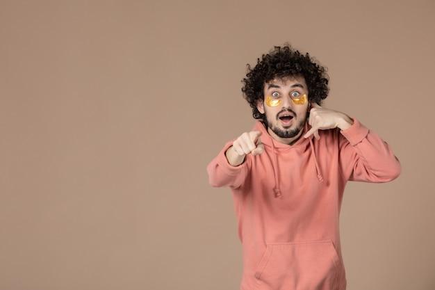 Vorderansicht junger mann mit augenflecken imitiert telefonanruf auf braunem hintergrund massage gesichtsbehandlung spa haut hautpflege schönheit