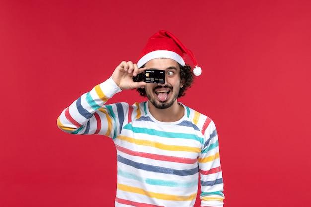 Vorderansicht junger mann mit bankkarte, die lustiges gesicht auf roter wand rotes männliches feiertagsgefühl macht