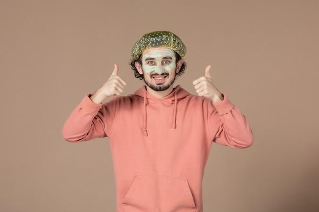 Vorderansicht junger mann mit bauschiger kappe auf braunem hintergrund salon hautpflege hauttherapie haar spa massage