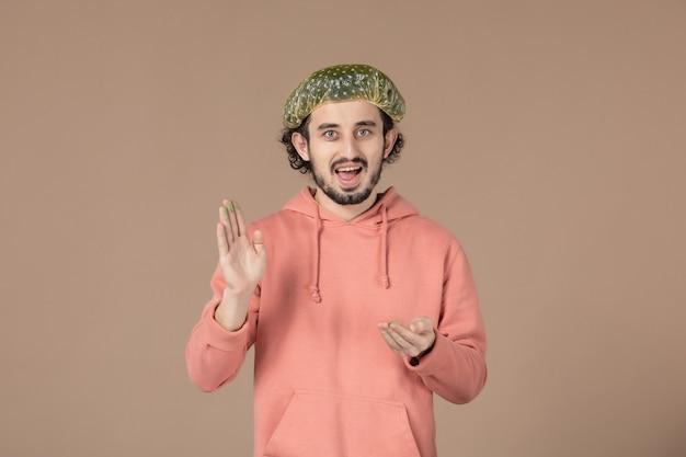 Vorderansicht junger mann mit bauschiger kappe auf braunem hintergrund salon hautpflege massage hauttherapie haar gesichtsbad