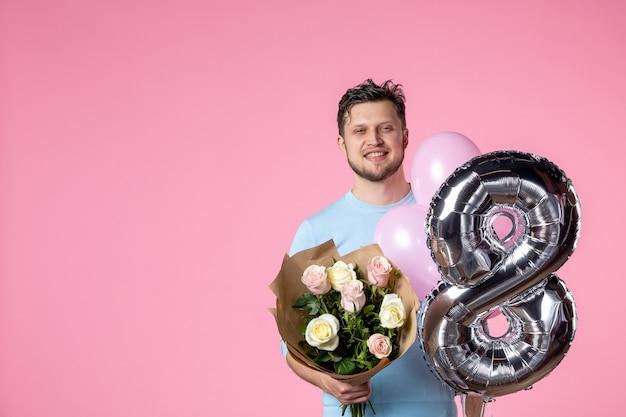 Vorderansicht junger mann mit blumen und luftballons als märz auf rosa hintergrund vorhanden gleichheit ehe liebe frauentag weiblich sinnlich horizontal