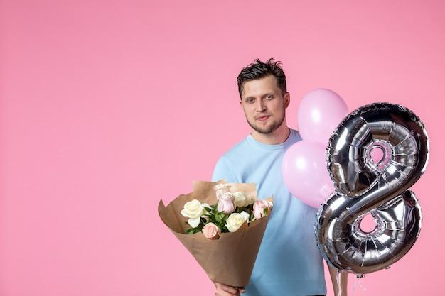Vorderansicht junger mann mit blumen und luftballons als marsch auf rosa hintergrund gleichheit ehe liebe frauentag weiblich sinnlich