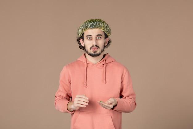 Vorderansicht junger mann mit bouffant-kappe auf braunem hintergrund hautpflege massage spa hauttherapie salon haar gesichtsbehandlung