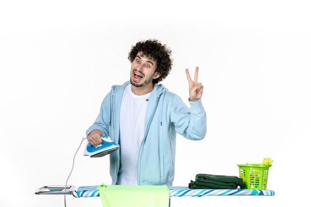 Vorderansicht junger mann mit bügeleisen auf weißem hintergrund bügeln farbe mann wäsche kleidung hausarbeit reinigung emotion