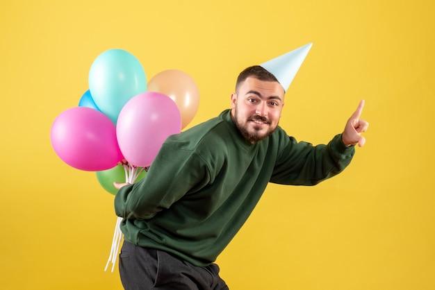 Vorderansicht junger mann mit bunten luftballons auf gelbem hintergrund