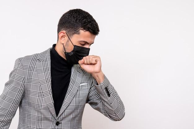 Vorderansicht junger mann mit dem schwarzen maskenhusten, der auf weißem lokalisiertem hintergrund steht