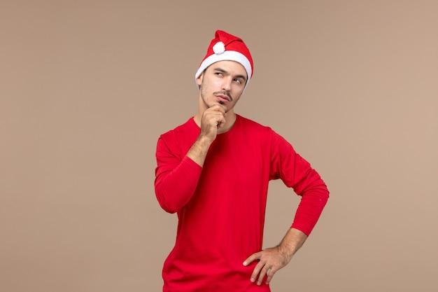 Vorderansicht junger mann mit denkendem ausdruck auf braunem hintergrund männlicher farbemotionsfeiertag